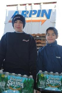 Cameron, left, and Collin Mosher help load a truck with bottled water bound for the Philippines.